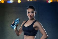 Woman drinking water from bottle in gym Royalty Free Stock Image