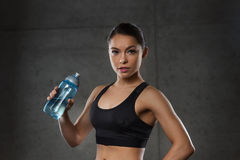 Woman drinking water from bottle in gym Royalty Free Stock Photos