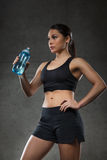 Woman drinking water from bottle in gym Royalty Free Stock Photography