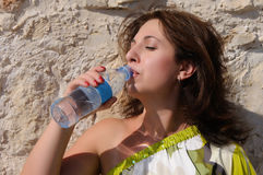 Woman drinking water from the bottle outdoor Stock Photos