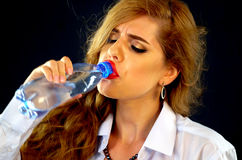 Woman drinking water from bottle . Thirsty Girl business suit drink . Stock Photo