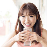 Woman drinking water at cafe. Happy Asian girl drinking mineral water at outdoor cafe. Young woman living lifestyle Stock Photography