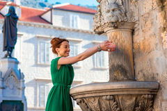 Woman drinking water from classical fountain in Stock Photo