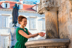 Woman drinking water from classical fountain in Stock Photography