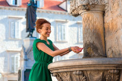 Woman drinking water from classical fountain in Royalty Free Stock Photo