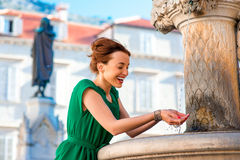 Woman drinking water from classical fountain in Stock Image