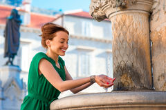 Woman drinking water from classical fountain in Stock Photos