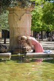 Woman drinking water and cooling from a source a hot day in Cord Stock Photos