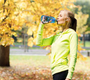 Woman drinking water after doing sports outdoors Royalty Free Stock Images