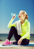 Woman drinking water after doing sports outdoors Stock Photo