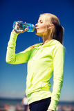 Woman drinking water after doing sports outdoors Stock Image
