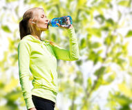 Woman drinking water after doing sports outdoors Royalty Free Stock Photography