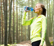 Woman drinking water after doing sports outdoors Royalty Free Stock Photos
