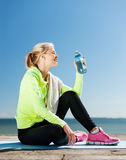 Woman drinking water after doing sports outdoors Stock Photos