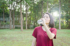 Woman drinking water after excercise. Asian woman drinking water from bottle after excercise Stock Image