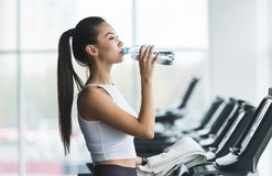 Woman drinking water after exercising on treadmill. In gym royalty free stock photo