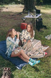 Woman drinking water with friend in campsite. Young women drinking bottle of water with her happy friend sitting in campsite into forest stock images