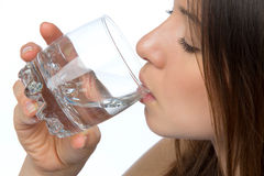 Woman drinking water from glass. Isolated against white background stock photos