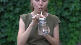 Woman drinking water from glass mug, choosing reusable safe materials, ecology