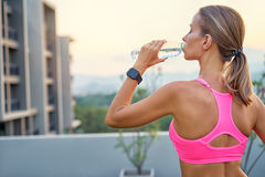 Woman drinking water. Healthy lifestyle and technology. Close up of young pretty woman drinking water with digital smart tracker outdoors Royalty Free Stock Photography