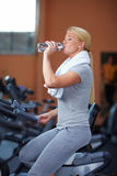Woman drinking water on hometrainer Stock Images