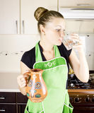 Woman drinking water in the kitchen Royalty Free Stock Photo