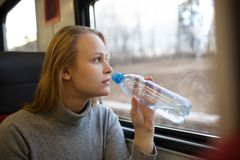 Woman drinking water and looking out train window Royalty Free Stock Photos