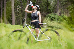 Woman drinking water next to her bike Stock Photos
