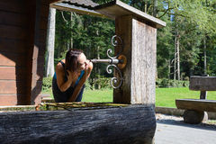 Woman drinking water from an old well Royalty Free Stock Photography