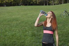 Woman drinking water during outdoor fitness workout Royalty Free Stock Images