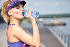 Woman drinking water after outdoor workout Royalty Free Stock Images