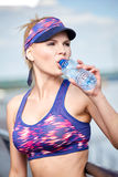 Woman drinking water after outdoor workout Royalty Free Stock Photo