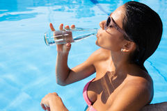 Woman drinking water outdoors Stock Photo