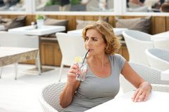 Woman drinking water at outdoors restaurant Stock Images