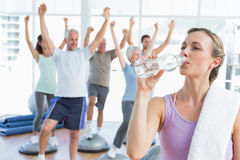 Woman drinking water with people stretching hands at fitness studio Stock Photography
