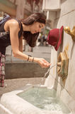 Woman drinking water at the public street fountain Royalty Free Stock Image