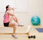 Woman drinking water and resting on bench. In fitness studio Royalty Free Stock Image