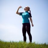 Woman drinking water after running outdoors royalty free stock photo