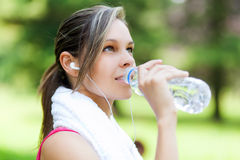Woman drinking water after running Stock Photography