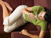 Woman drinking water on sofa Royalty Free Stock Image