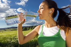 Woman drinking water after sport activities Stock Photos