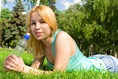 Woman drinking water on the summer glade Royalty Free Stock Image