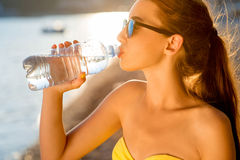 Woman drinking water from transparent bottle on Stock Image