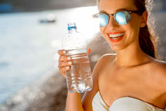 Woman drinking water from transparent bottle on Royalty Free Stock Image