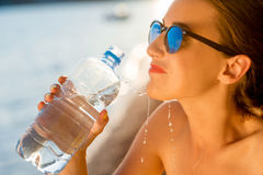 Woman drinking water from transparent bottle on Royalty Free Stock Photos