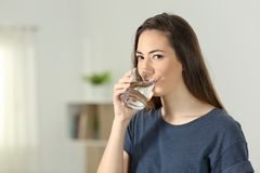 Woman drinking water and looking at you. Woman drinking water in a transparent glass and looking at you at home Royalty Free Stock Photography