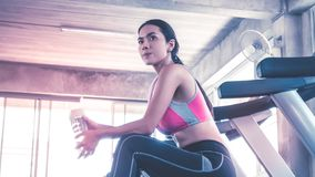 Woman drinking water on treadmill workout in fitness gym stock images