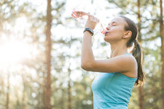 Woman drinking water after work out exercising on sunset evening Royalty Free Stock Photo
