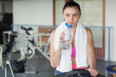 Woman drinking water while working out at spinning class Stock Photo