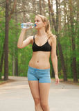 Woman drinking water after workout Royalty Free Stock Photos